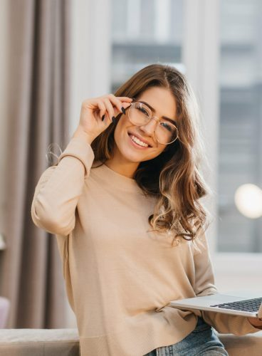 cute-girl-beige-shirt-touching-glasses-holding-laptop-with-smile-min